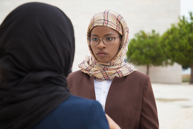 Serious muslim female employee talking to colleague Free Photo