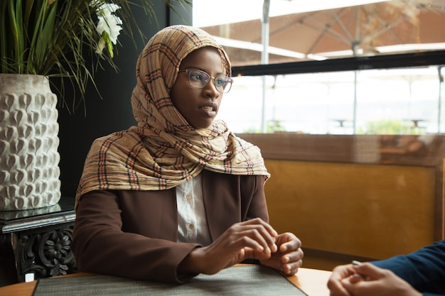 Serious muslim female employee talking to coworker Free Photo