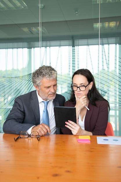 タブレットでコンテンツを一緒に見て、画面を見ている深刻なオフィスの同僚。 無料写真