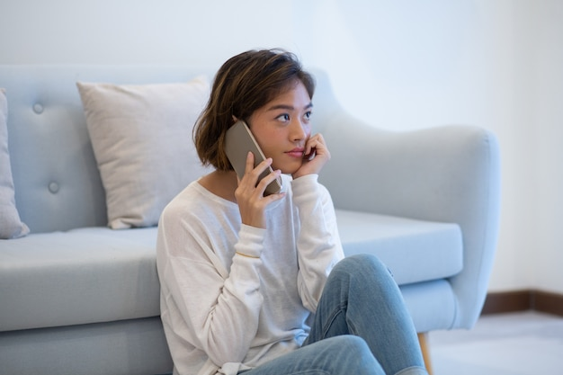 Serious pensive asian customer reaching support by phone Free Photo