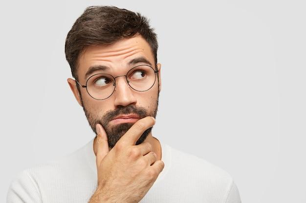 Uomo barbuto serio e pensieroso con una folta barba incolta, tiene il mento e guarda pensieroso da parte, contempla qualcosa mentre è concentrato nell'angolo superiore destro Foto Gratuite