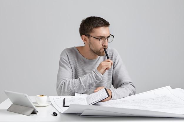 심각한 생각에 잠겨있는 남성 엔지니어가 손에 펜과 노트북을 유지하고 회의를 계획합니다. 무료 사진
