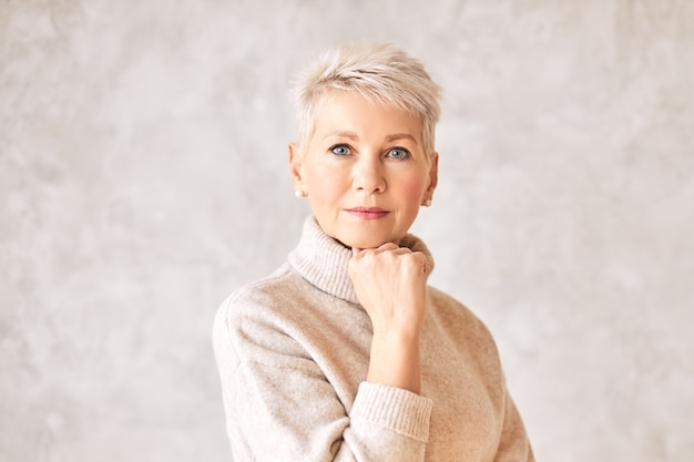 Serious pensive middle aged female wearing warm pullover and pearl earrings looking Free Photo