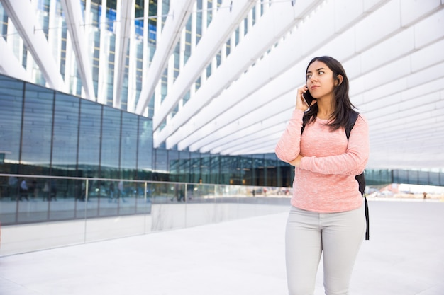 Serious pensive student girl with satchel talking on phone Free Photo