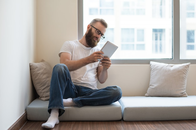 Serious pensive young man in glasses reading online article Free Photo