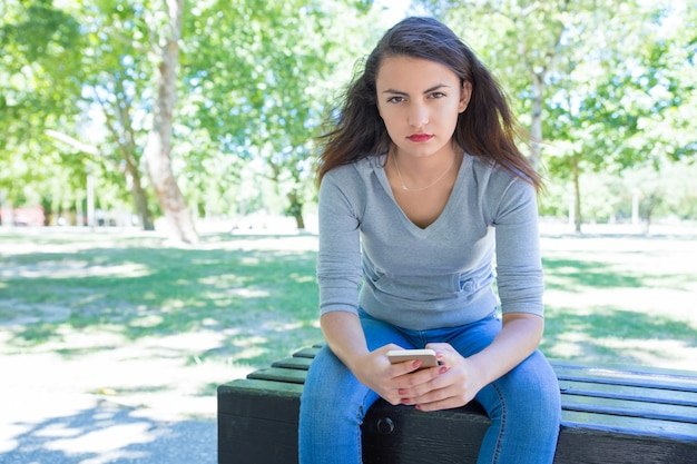 Serious pretty young lady using smartphone on bench in park Free Photo
