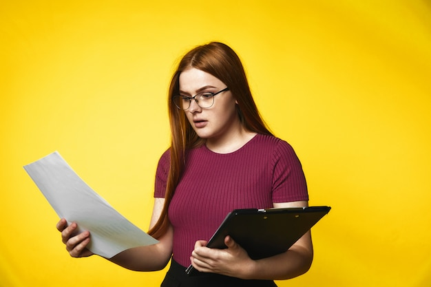 Serious redhead caucasian girl is holding folder with documents in hands with surprised face Free Photo