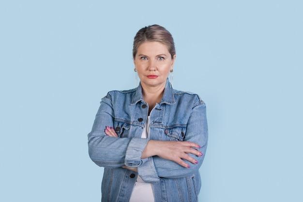 青い壁に交差した手でポーズをとってジーンズのコートを着ているブロンドの髪を持つ深刻な年配の白人女性 Premium写真