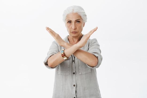 Серьезная строгая бабушка показывает крестный жест, запрещает или не одобряет действия Бесплатные Фотографии