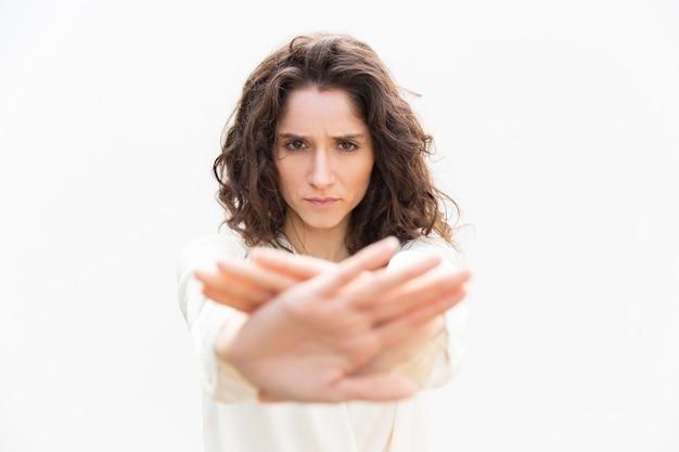 Donna severa seria nel fare gesto di arresto della mano Foto Gratuite