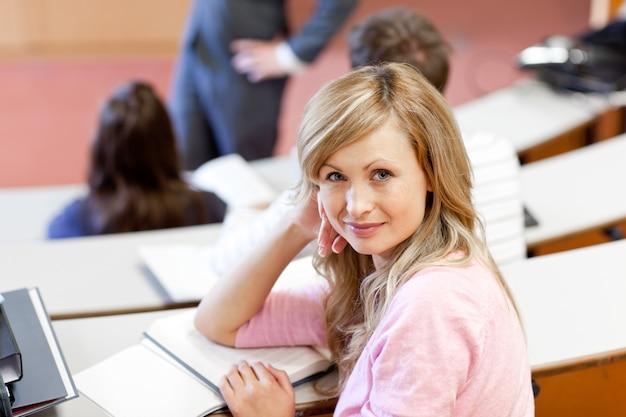 Серьезные ученики слушают своего учителя в университете Premium Фотографии