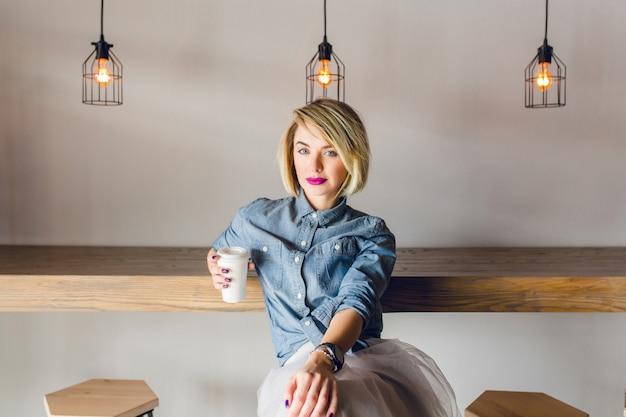 ブロンドの髪とピンクの唇が木の椅子とテーブルのあるコーヒーショップに座っている深刻なスタイリッシュな女の子。彼女は一杯のコーヒーを持っています 無料写真