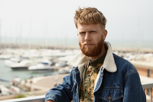 Серьезный стильный хипстерский парень в синей джинсовой куртке, щурясь от яркого света греха Бесплатные Фотографии