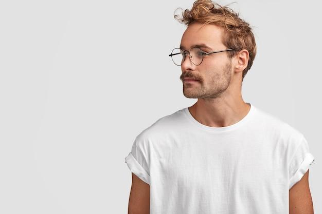 真面目でスタイリッシュなヒップスターは自信を持って脇を向いて、頭を横に向け、何かを遠くに見て、丸い眼鏡をかけています 無料写真