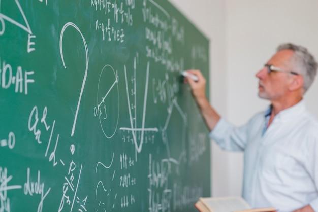 Serious teacher chalking on blackboard in soft focus Premium Photo