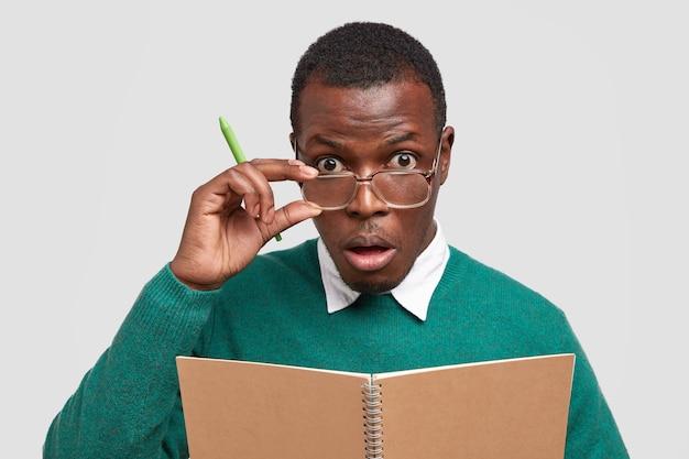 Insegnante serio tiene la mano sulla montatura degli occhiali, tiene la penna, sorpreso dall'eccellente risposta degli studenti all'esame, utilizza il blocco note per scrivere appunti Foto Gratuite