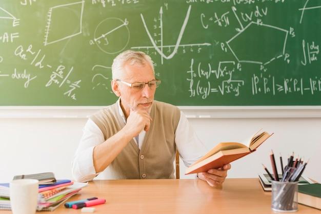 Serious teacher reading book Free Photo