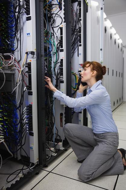 Serious technician talking on phone while analysing server Premium Photo