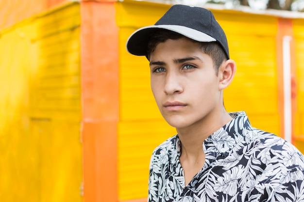 Serious teenage boy wearing cap looking at camera Free Photo