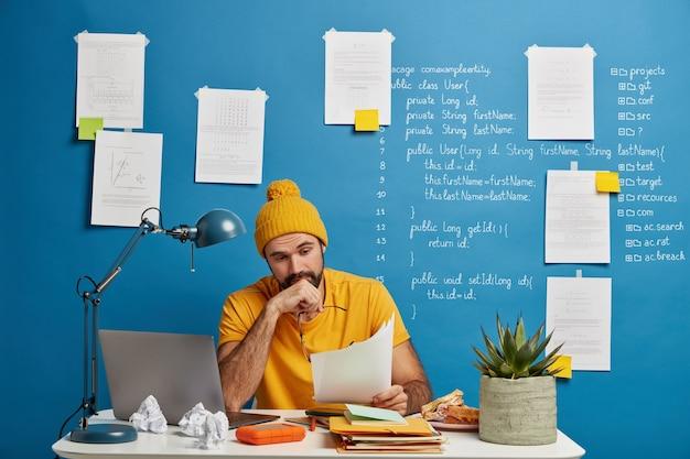 Il manager maschio serio con la barba lunga in abito giallo esamina la documentazione finanziaria Foto Gratuite