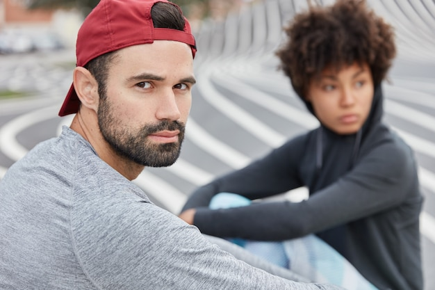 Serious unshaven man in stylish red cap, grey sweathshirt, enjoys leisure time, breathes fresh air, afro girl in background Free Photo