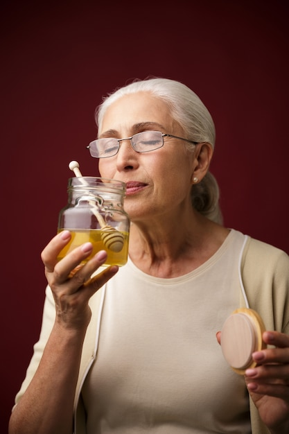 Serious woman holding honey Free Photo