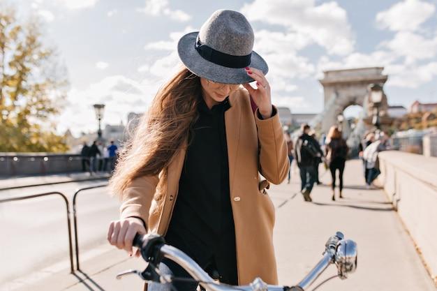 Серьезная женщина в модном бежевом пальто катается по городу осенним утром Бесплатные Фотографии