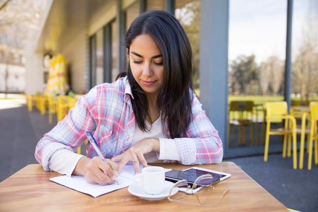 Serious woman making notes in outdoor cafe Free Photo
