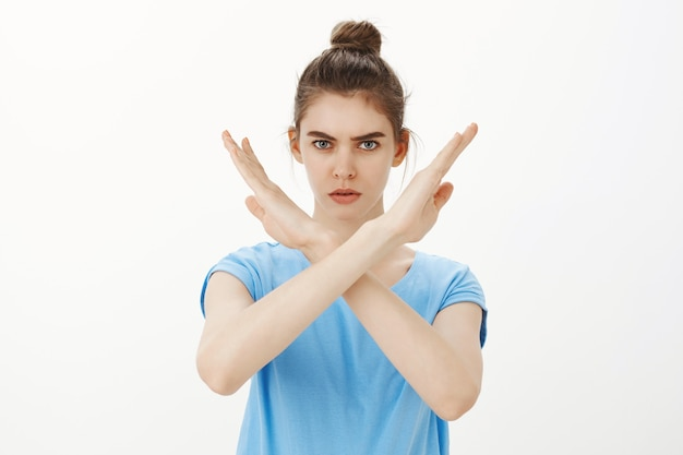 Serious woman making stop cross gesture, rejecting or forbidding something, disapprove action Free Photo