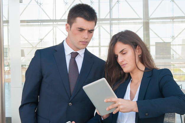 Serious woman showing concentrated man data on tablet Free Photo