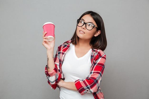 一杯のコーヒーを保持している灰色の壁の上に立っている深刻な女性。 無料写真