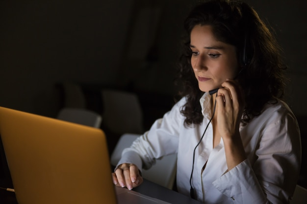 Serious woman with headset using laptop Free Photo