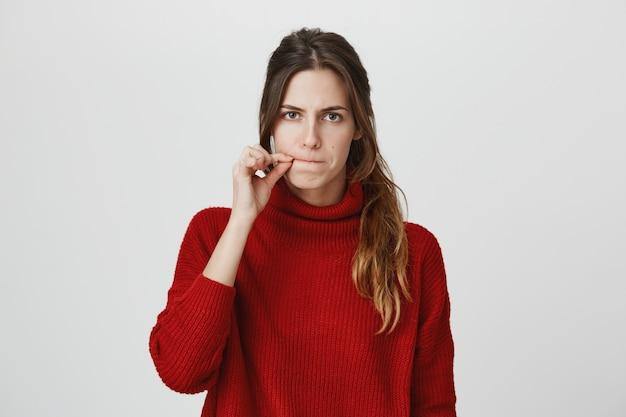 Serious woman zipping mouth, keep secret Free Photo
