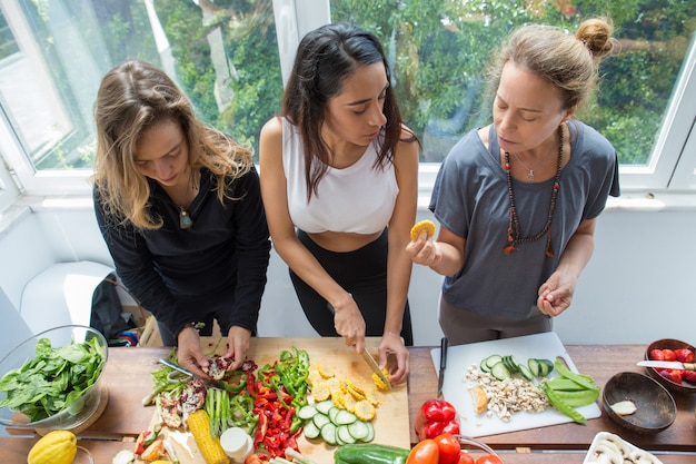 Donne seri che chiacchierano e che tagliano le verdure in cucina Foto Gratuite