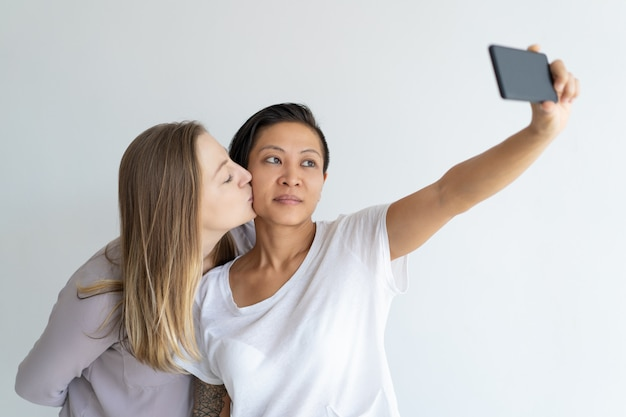 Serious women kissing and taking selfie photograph Free Photo