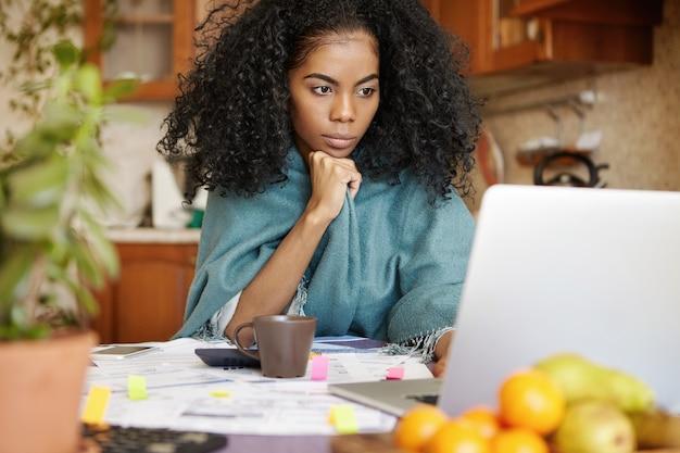 Серьезная молодая афроамериканка в теплой одежде занимается финансами ночью Бесплатные Фотографии