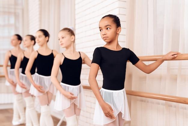 Serious young ballerinas stand along ballet barre. Premium Photo