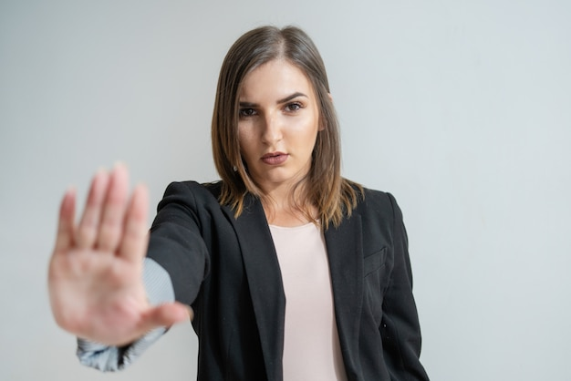 Serious young caucasian businesswoman showing stop gesture Free Photo