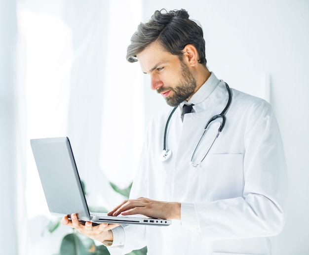 Serious young doctor browsing laptop Free Photo