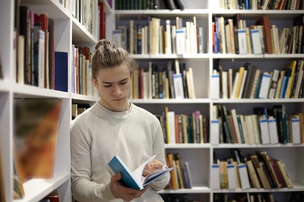 本屋に立って、手に教科書からの抜粋を読んで、本でいっぱいの白い棚に寄りかかってセーターを着ている真面目な若い男 無料写真