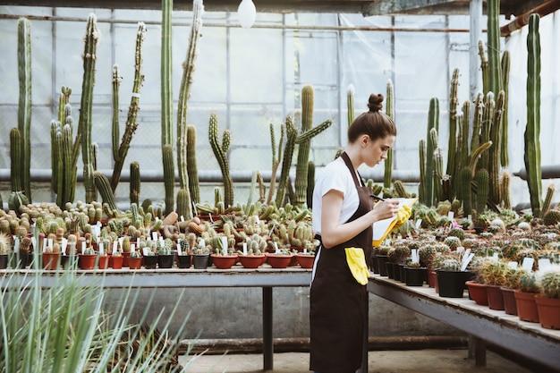 クリップボードを保持している温室に立っている深刻な若い女性 無料写真
