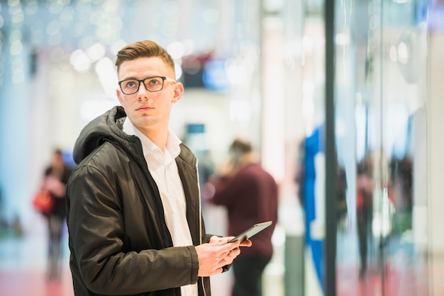 Serious young man holding digital tablet in hand looking away Free Photo