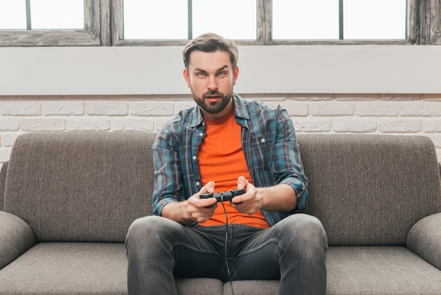Serious young man sitting on sofa playing video game Free Photo