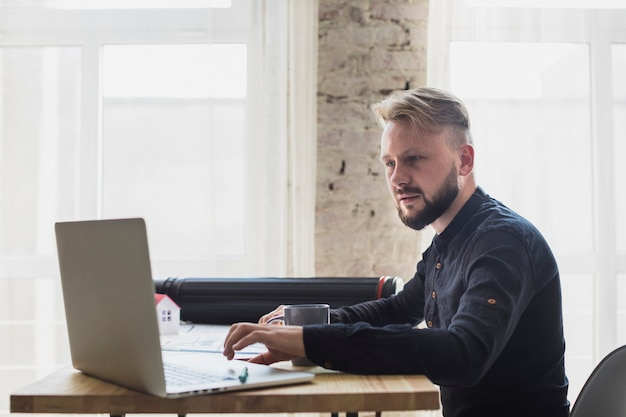 Serious young man working on laptop at office Free Photo