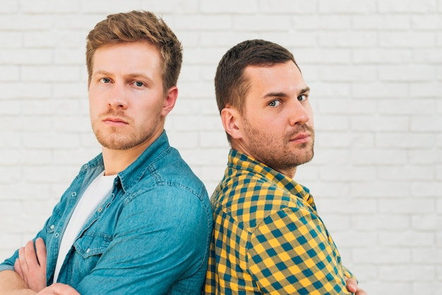 Serious young men standing back to back looking at camera Free Photo
