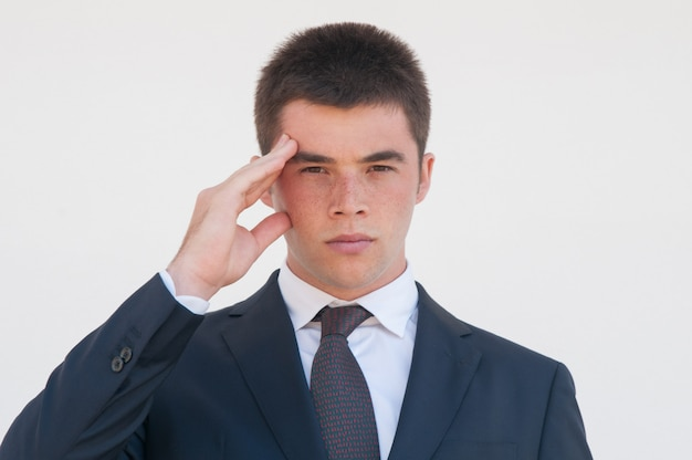 Serious young office worker touching head Free Photo