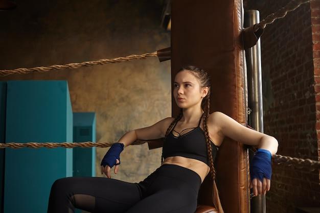 Grave kickboxer femminile giovane professionista che indossa abbigliamento sportivo alla moda e bende sulle mani, riposando dopo l'allenamento Foto Gratuite