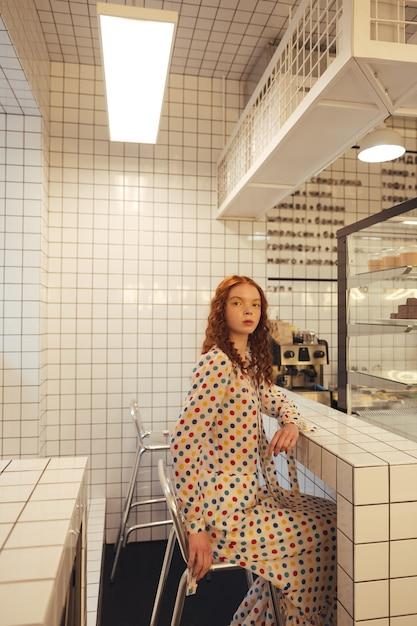 Signora riccia della giovane testarossa seria che si siede in caffè Foto Gratuite
