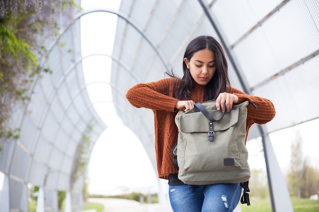 Serious young woman finding phone in bag outdoors Free Photo
