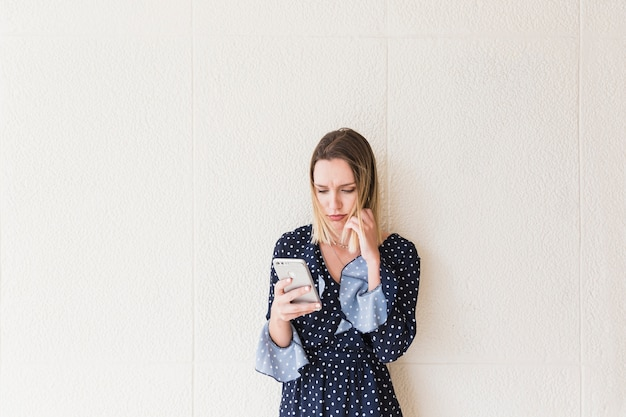 Serious young woman holding cellphone Free Photo